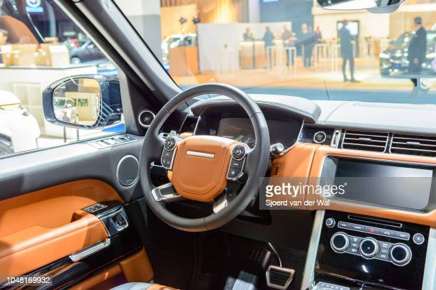 Interior on a Land Rover Discovery crossover SUV fitted with brown leather seats, aluminium details and a large information display on the dashboard...