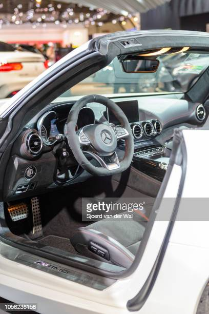 Interior on a MercedesAMG GT Roadster open sports car with black leather seats and red piping and an information display on the dashboard on display...