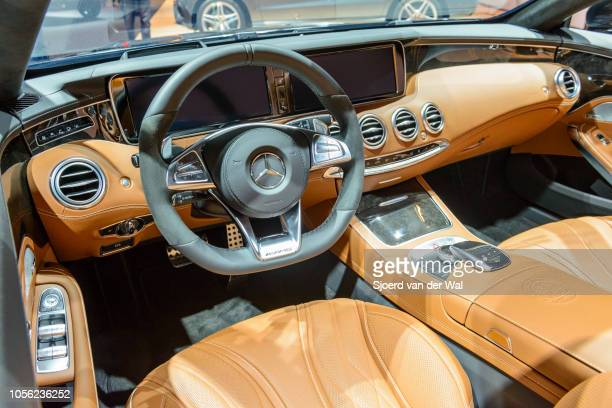 Interior on a Mercedes-AMG S 63 Cabriolet 4Matic luxury convertible car with brown leather seats and large information display son the dashboard on...