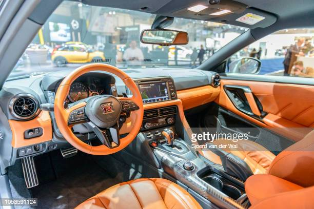 Interior on a Nissan GT-R high performance sports car with brown leather trim and information displays on the dashboard on display at Brussels Expo...