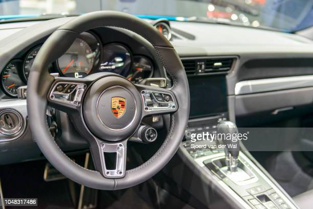 Interior on a Porsche 911 Cabriolet convertible sports car fitted with black leather seats and a large information display on the dashboard on...