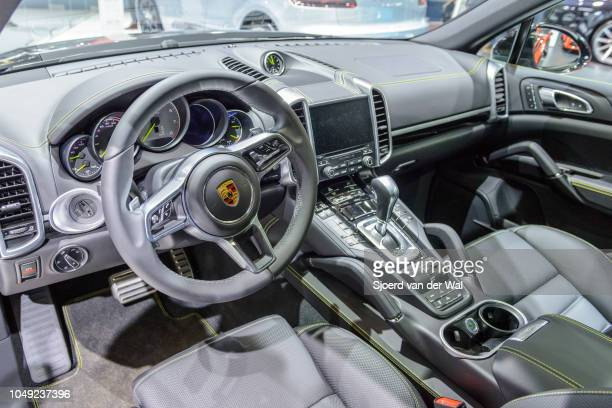 Interior on a Porsche Cayenne S EHybrid plugin hybrid luxury SUV with black leather trim and information displays on the dashboard on display at...