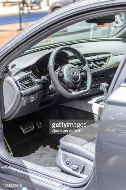 Interior on an Audi A6 Avant luxury executive station wagon with black leather seats and information displays on the dashboard on display at Brussels...