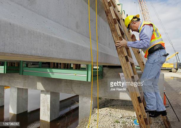 Interior Secretary Ken Salazar cllimbs down from looking at the construction work being done on the Tamiami Trail Bridge Project in the Florida...