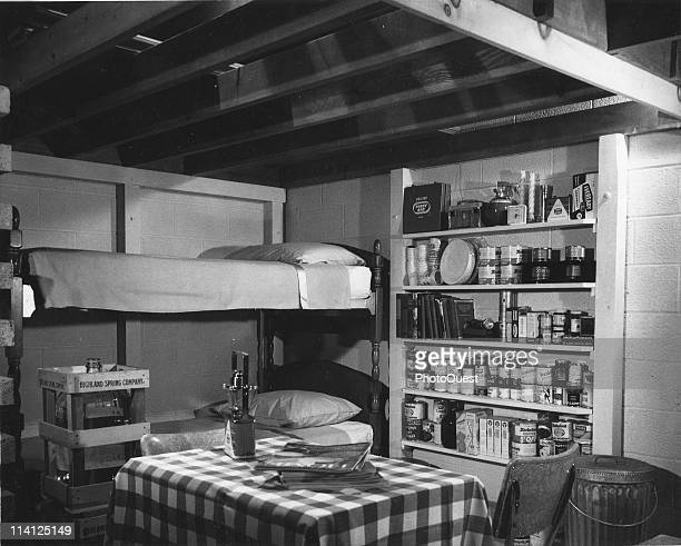 Interior view of a basement family fallout shelter 1960s Among the visible supplies are a 14day supply of water and canned food a batteroperated...