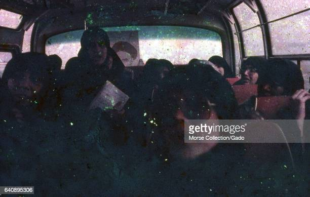Interior view of a bus filled with Iranian female Basij members , wearing black chadors and holding pictures of the Ayatollah Khomeini, in Iran,...