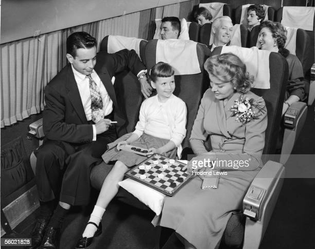 Interior view of a commercial passenger plane shows a woman as she contemplates a move in a checkers game she is losing to a young girl while a man...