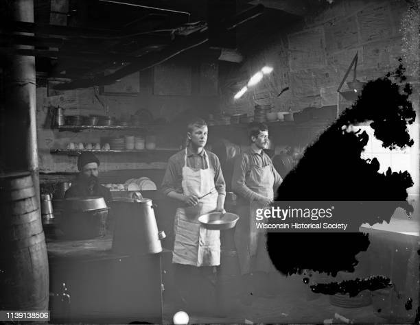 Interior view of a kitchen in a logging camp with light coming in from a window on the far right Black River Falls Wisconsin 1890 Two men are posing...