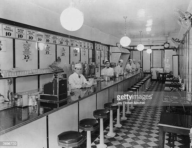 Interior view of a luncheonette with a staff of six young men standing behind the counter in white shirts bow ties and caps Menu selections including...