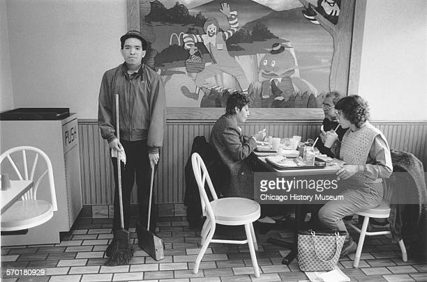 Interior view of a McDonald's restaurant showing an employee sweeping the floor and a group of patrons eating Chicago Illinois circa 1987
