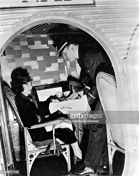 Interior view of a steward serving a passenger on a United Airlines plane late 1920s