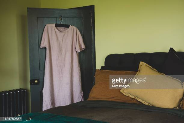 interior view of bedroom with light green walls, double bed with and pale pink linen nightgown on hanger over door. - double bed stock pictures, royalty-free photos & images
