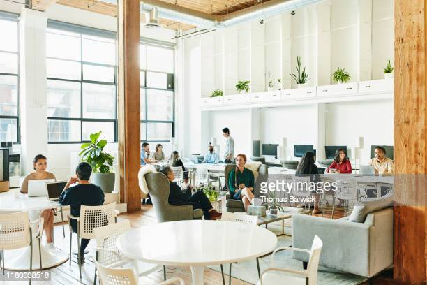 interior view of businesspeople working in coworking office - community work stock pictures, royalty-free photos & images