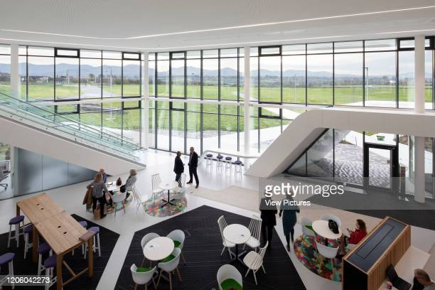 Interior view of cafe with Snowdonia National Park in background. Menai Science Parc, Bangor, United Kingdom. Architect: FaulknerBrowns, 2019.
