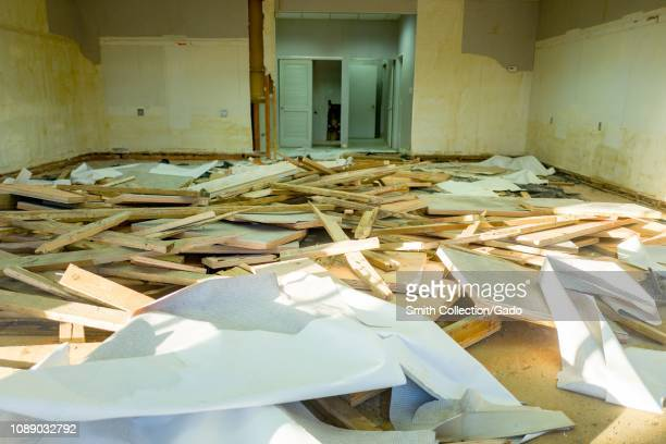 Interior view of closed or out of business retail store whose interior is in the process of being demolished with debris and wooden boards in a large...