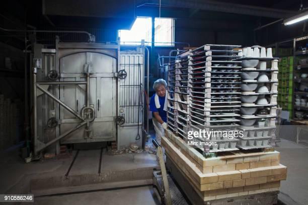 Interior view of Japanese porcelain workshop, man preparing large stack of porcelain objects for kiln.