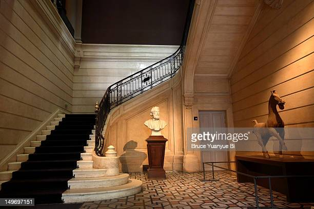Interior view of Musee Cernuschi with bust of founder Henri Cernuschi next to staircase.