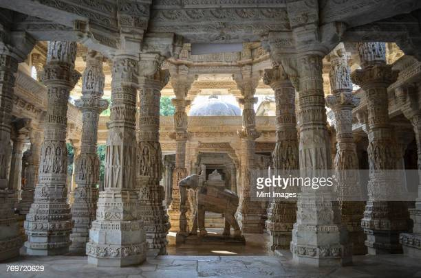 interior view of ranakpur jain temple, ranakpur. carvings and marble columns and a statue of an elephant.  - jain temple stock photos and pictures
