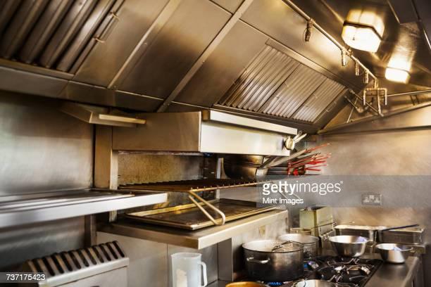 interior view of restaurant kitchen, pots on stovetop, grill and extractor hood. - afzuigapparaat stockfoto's en -beelden