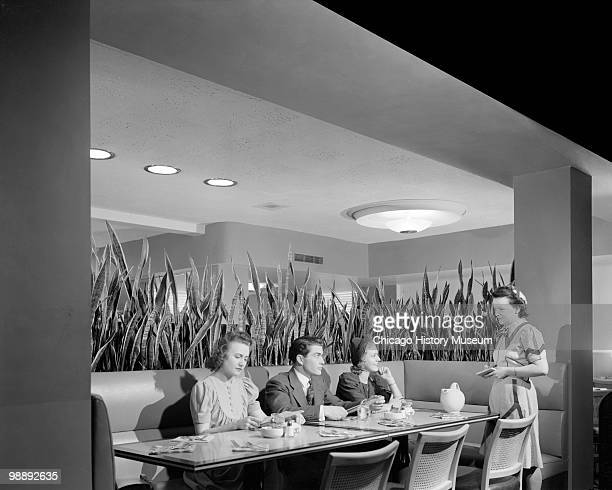 Interior view of the Blackstone Hotel showing three people sitting at a booth with a waitress standing beside them Omaha NE 1941 The hotel was...