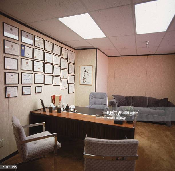 Interior view of the empty office of Alan J Winters MD complete with a desk chairs a sofa and a large number of framed diplomas on the wall 1980s