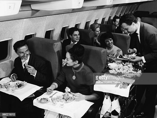 Interior view of the first class compartment of a commercial passenger plane shows in the foreground a welldressed couple as they smile and enjoy...