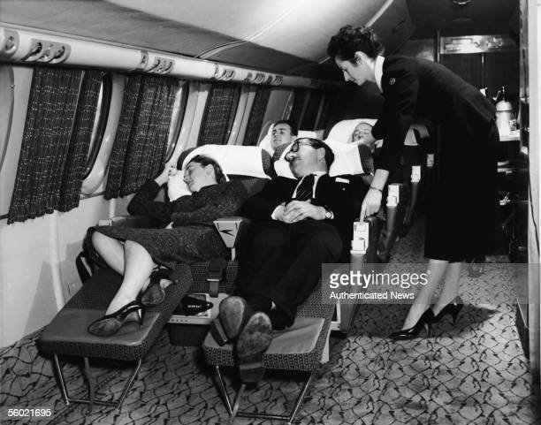 Interior view of the first class compartment of a commercial passenger plane shows a flight attendant as she bends forward to adjust the seat of a...