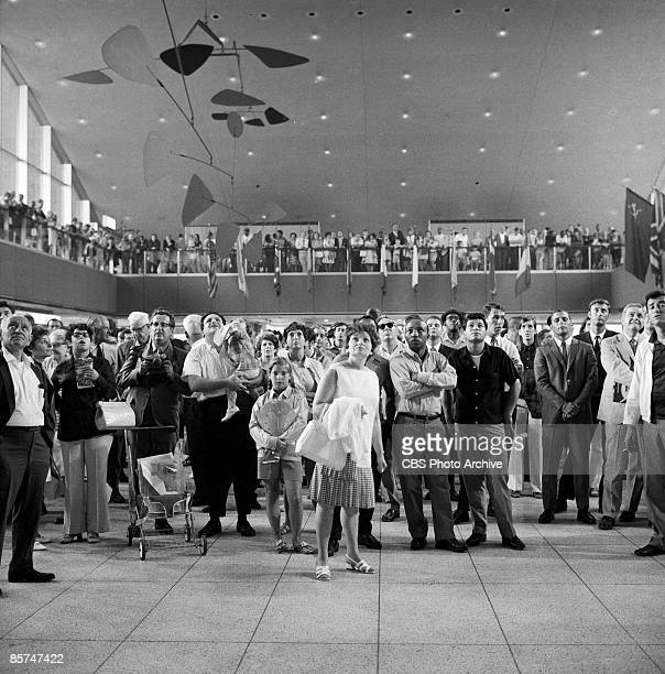 Interior view of the International Arrival Building at John F. Kennedy International Airport shows a crowd of passengers as they stand under a...