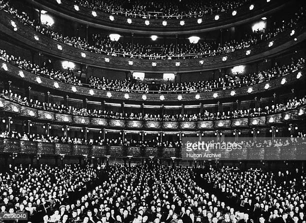 Interior view of the Metropolitan Opera House filled with patrons in the auditorium and in all of the balconies at the rear of the theater, New York...