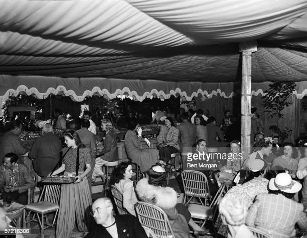 Interior view of the night club 'Taboo' shows patrons as they sit and drink and smoke Worth Avenue Palm Beach Florida 1942