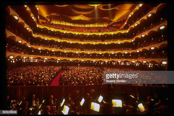 Interior view overlooking the orchestra pit of a capacity crowd for a performance at the Metropolitan Opera House