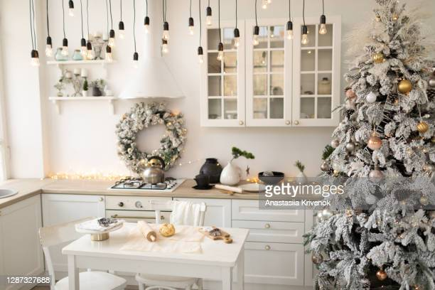 interior white kitchen with christmas decor and decorated fir tree. - public celebratory event stock pictures, royalty-free photos & images