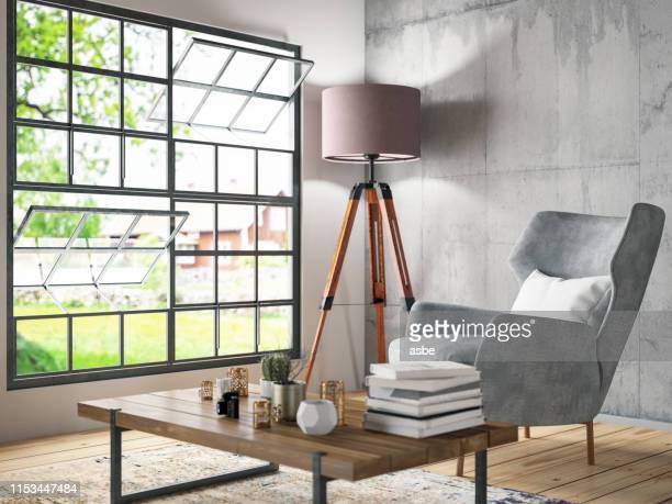 interieur met fauteuil en boeken - ottomane stockfoto's en -beelden