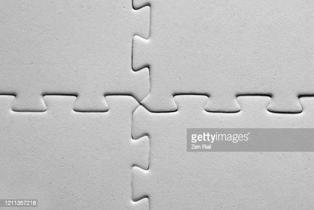 interlocked four white jigsaw pieces - continuidade imagens e fotografias de stock