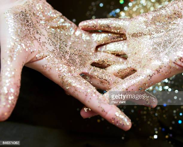 interlocking fingers covered in gold oil and glitter