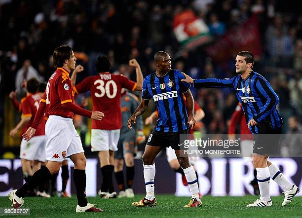 Inter-Milan's Samuel Eto'o and Christian Chivu walk as AS Roma's players celebrate after their Serie A football match in Rome's Olimpic Stadium on...