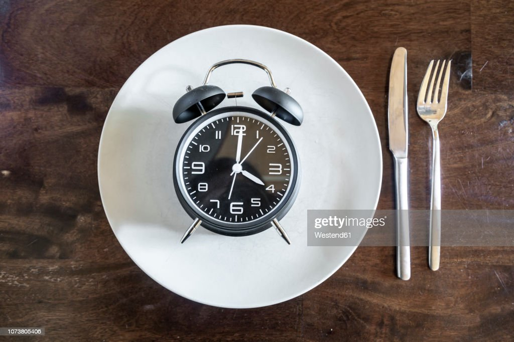 Intermittent fasting, trend 16:8 fasten, alarm clock on plate : Stock Photo