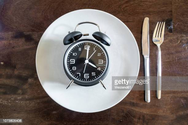 intermittent fasting, trend 16:8 fasten, alarm clock on plate - fasting activity stock pictures, royalty-free photos & images