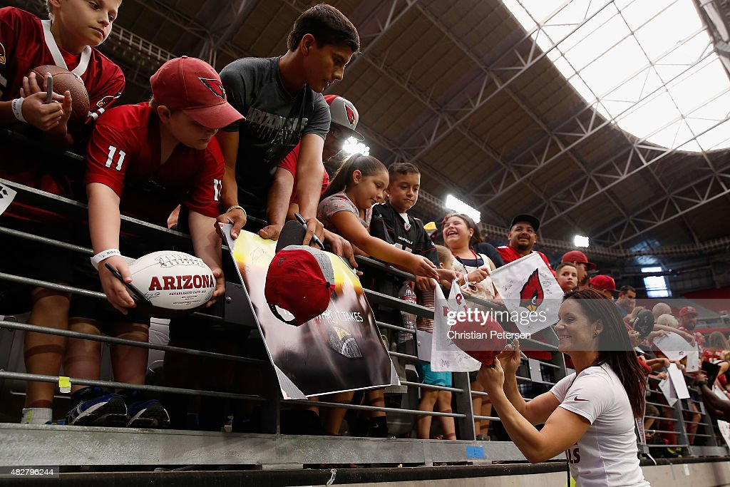 Intern linebacker coach Jen Welter of the Arizona Cardinals signs autographs for fans following the team training camp at University of Phoenix Stadium on August 2, 2015 in Glendale, Arizona.