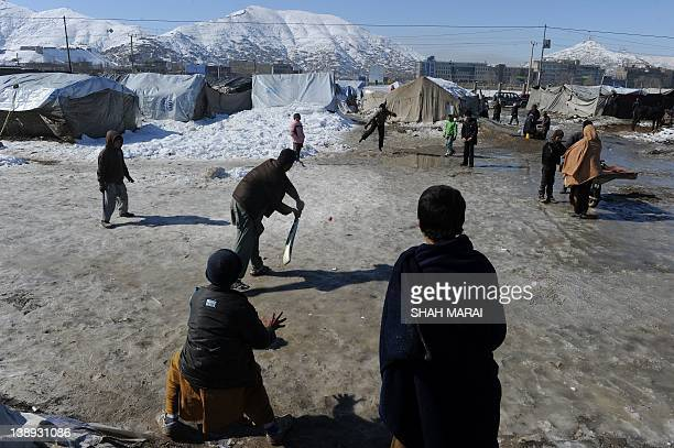 Internally displaced Afghan children play cricket outside their tent at a refugee camp in Kabul on February 14 2012 Cricket has become the top sport...