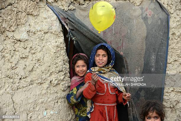 TOPSHOT Internally displaced Afghan children play outside their temporary home at a refugee camp in Kabul on December 16 2016 / AFP / NOORULLAH...