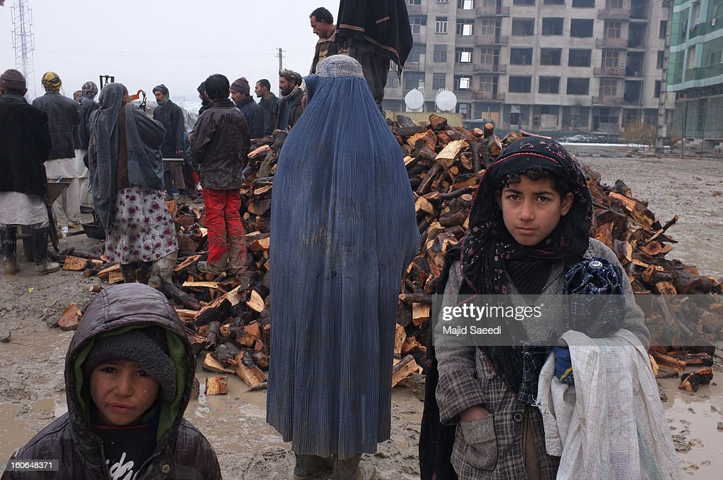 Internally displaced Afghans wait to receive aid donations at Chamand babrak Camp, on February 3, 2013 in Kabul, Afghanistan. According to the UN refugee agency, Afghanistan's internally displaced population has reached half a million, although the actual figure is believed to be much higher.