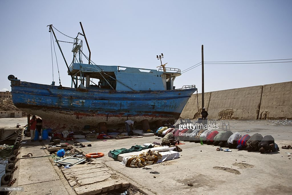 Internally displaced African migrant workers pray towards Mecca while living in misreable conditions in a deserted dry dock port filled with the wrecks of unseaworthy boats that have become a home to a thousand stranded guest workers on August 31 2011 in Tripoli, Libya. Many black Africans are accused by Libyan Rebels of being mercentaries hired by former Libyan dictator Moummar Gaddafi. Many have lost their passports or can not face or afford going back to their own countries and are now stuck in Limbo waiting for hostilities in Libya to end. The stranded workers complain that every night Libyan youths with guns come to the camp and harrass the men, rob from them, and occassionaly rape several women.'