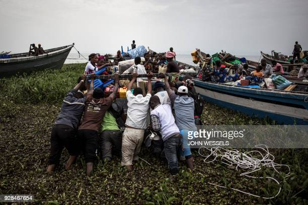 TOPSHOT Internally displaced Congolese push a boat out as its sets off to escape over Lake Albert to Uganda on March 05 2018 in Tchomia Displaced...