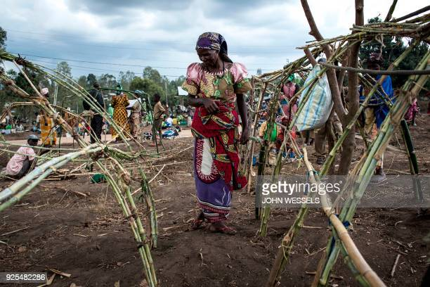 A Internally Displaced Congolese woman stands whist constructing a make shift shelter in a camp for IDP's on February 27 2018 in Bunia Twentythree...