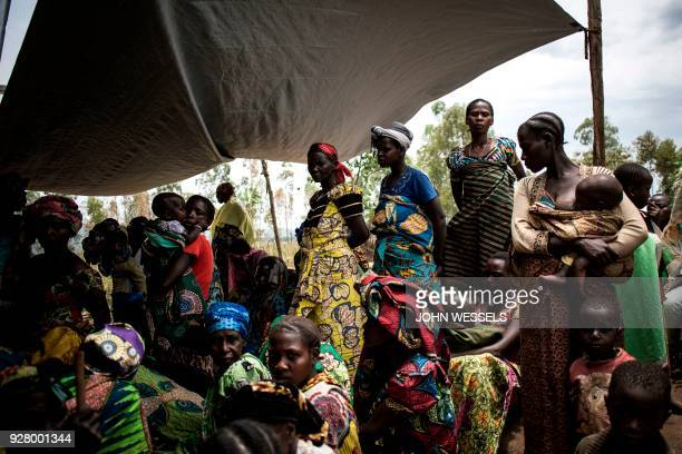 TOPSHOT Internally Displaced Congolese women and children wait outside a makeshift health clinic set up by international humanitarian NGO Doctors...
