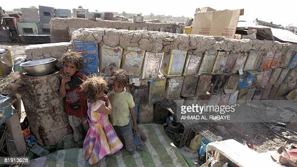 Internally displaced Iraqi Shiite children play next to a perimeter wall made from mud and cooking oil cans at a squatter settlement in southern...