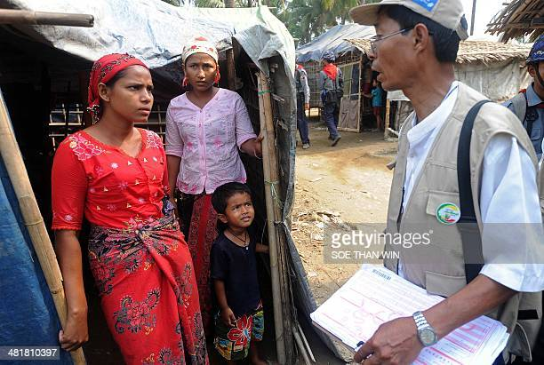 Internally displaced Muslim women answers questions from a census enumerator during a census at an Internally displaced camp at Theechaung village on...