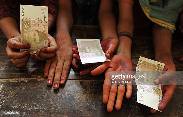 Internally displaced Pakistani children receive 10 Pakistani rupees as part of Eid AlFitr packages at a camp in Sukkur on September 9 2010 Pakistan's...
