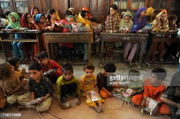 Internally displaced Pakistani children receive Eid Al-Fitr packages at a camp in Sukkur on September 7, 2010 prior to celebrations for the end of...